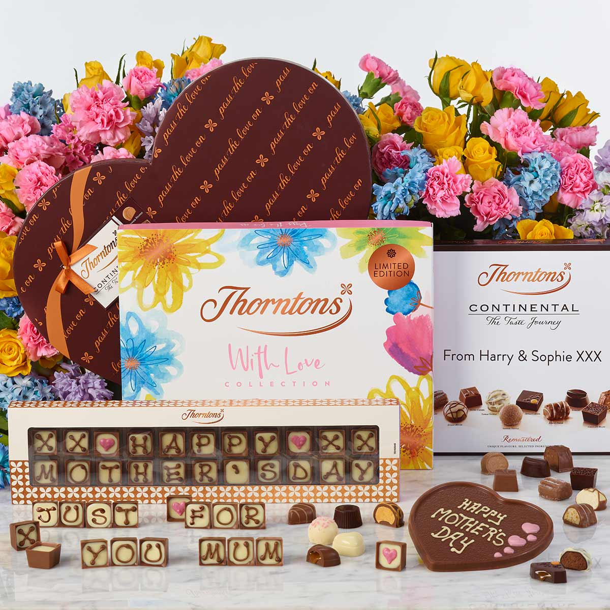 Assorted boxes of chocolates and colourful flowers behind them.