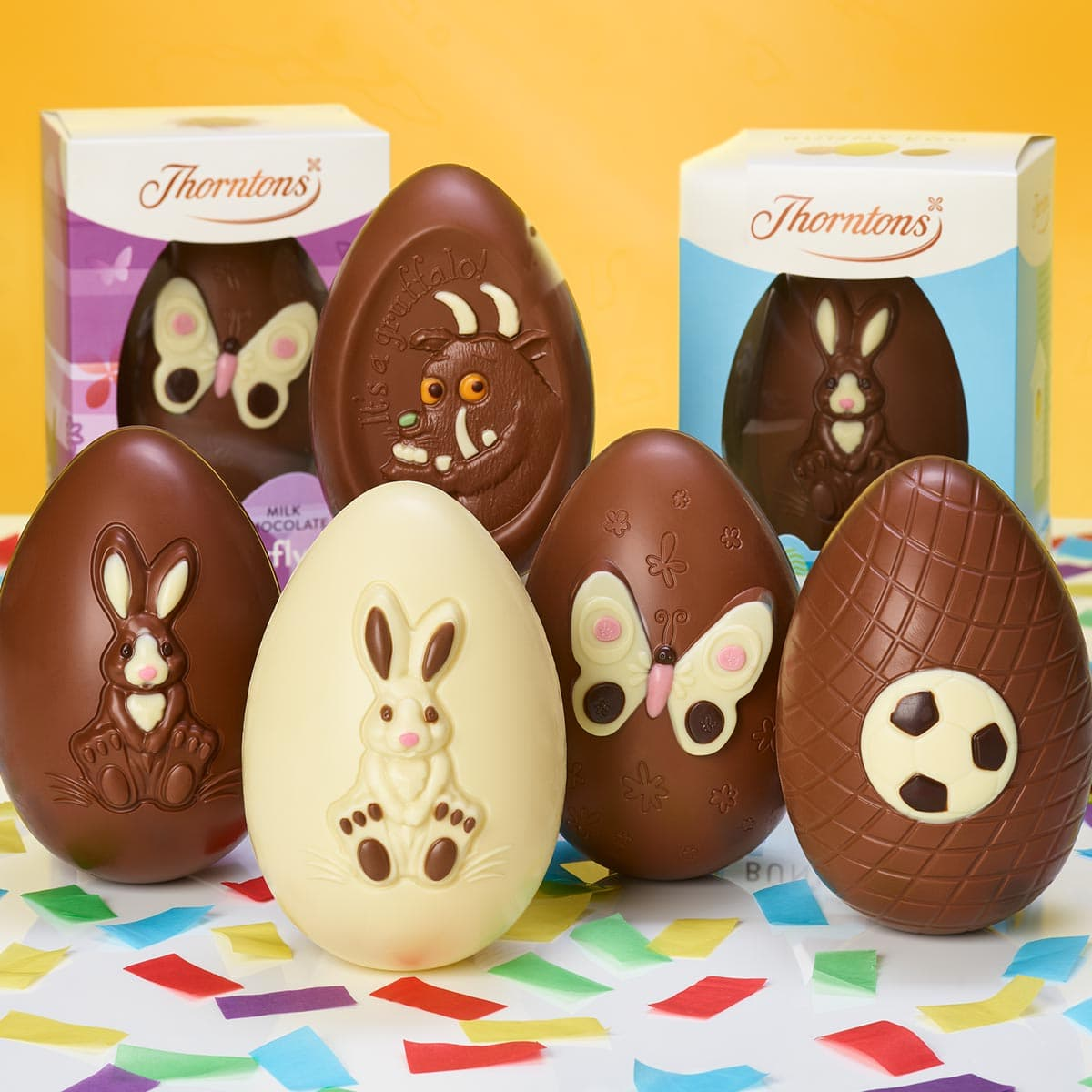 An assortment of Easter eggs in and out of boxes with bunny, butterfly and football images on them