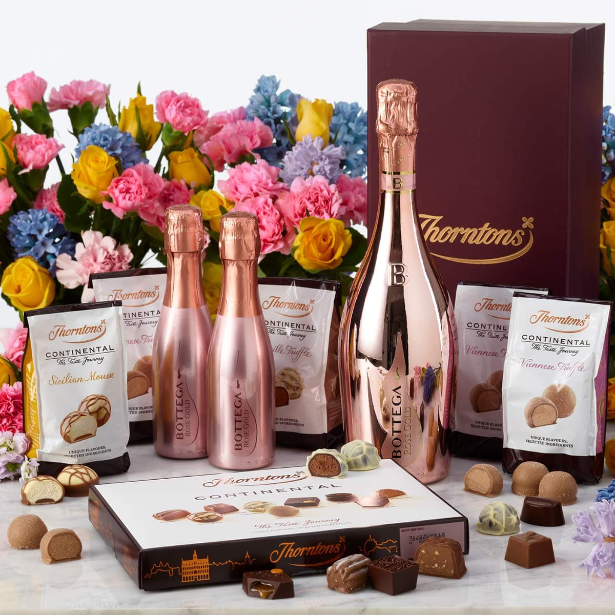 A large and two small pink prosecco bottles surrounded by flowers, bags of chocolates and a box of chocolates.